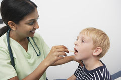Doctor Examining Patient Throat. Female doctor examining preadolescent patient throat in the clinic royalty free stock photos