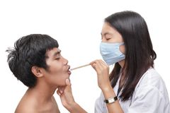 Doctor examining patient throat w spatula Royalty Free Stock Image