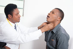 Doctor examining a patient. The doctor touches the throat of his patient whether he feels pain Royalty Free Stock Image