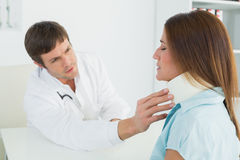 Doctor examining a patients neck in medical office Stock Images