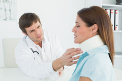 Doctor examining a patients neck in medical office Royalty Free Stock Photos