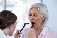 Doctor examining patients teeth with otoscope Royalty Free Stock Photos