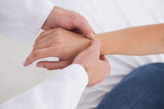 Doctor examining patients wrist. In his office Stock Images