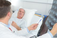 Doctor examining patients xray in hospital room royalty free stock image