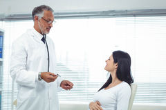 Doctor examining pregnant woman with a stethoscope Royalty Free Stock Photos