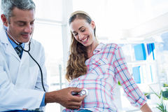Doctor examining a pregnant woman with a stethoscope Stock Photos
