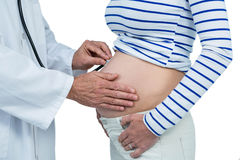 Doctor examining pregnant woman. Doctor using stethoscope while examining pregnant woman on white background Stock Photo