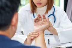 Doctor examining pulse of patient by hands, medical diagnosis co stock photos