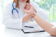 Doctor examining pulse of patient by hands, medical diagnosis co royalty free stock photo