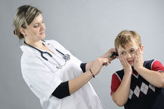 doctor examining school boy Royalty Free Stock Photos