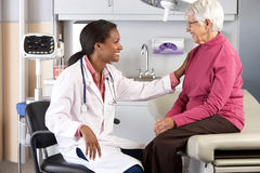 Doctor Examining Senior Female Patient Stock Images