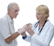Doctor examining senior man's bandaged wrist Stock Images