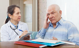 Doctor examining the senior patient Stock Images