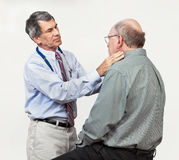 Doctor Examining Senior Patient's Swollen Glands. Mature male doctor examining senior male patient's neck for swollen glands. Plain neutral background royalty free stock photography