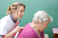 Doctor examining senior with stethoscope Stock Images