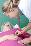 Doctor examining senior with stethoscope Royalty Free Stock Photo