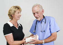 Doctor examining senior woman with hand in cast royalty free stock photo