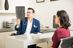 Doctor examining some x-rays with patient Stock Photography