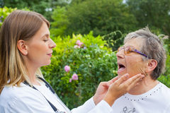 Doctor examining sore throat. Female medical doctor examining elderly women with sore throat in the garden stock photos
