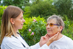Doctor examining sore throat. Female medical doctor examining elderly women with sore throat in the garden royalty free stock image
