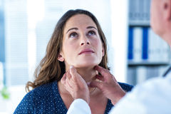 Doctor examining woman in clinic Stock Image
