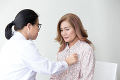 Doctor examining a woman in a hospital. Stethoscope doctor. Clos stock photography