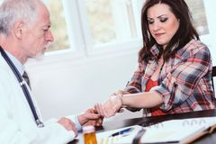 Doctor examining wrist of a female patient Stock Images
