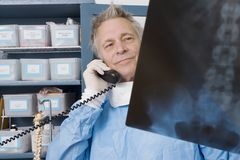 Doctor Examining X-Ray Report While Using Landline Phone Royalty Free Stock Image