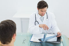 Doctor examining xray with patient at office Stock Photo