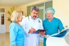 Doctor experimentado y personal médico que consultan sobre historial médico en hospital Foto de archivo libre de regalías