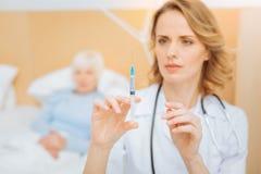 Doctor experto tranquilo que consigue listo para hacer una inyección necesaria Imagen de archivo libre de regalías
