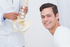 Doctor explaining anatomical spine to his patient Royalty Free Stock Photos
