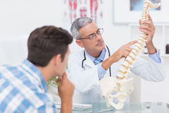 Doctor explaining anatomical spine to his patient Stock Images
