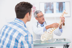 Doctor explaining anatomical spine to his patient Stock Photos