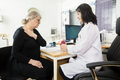 Doctor Explaining Anatomy To Senior Patient Suffering From Shoul. Female doctor explaining anatomy to senior patient suffering from shoulder pain in clinic stock photo
