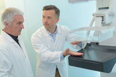 Doctor explaining another doctor how new xray machine works Stock Photo