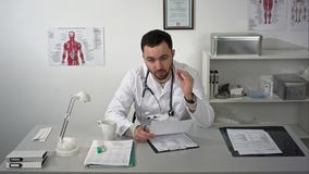 Doctor explaining at camera in medical office stock photography