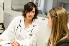 Doctor explaining diagnosis to her female patient Stock Photos