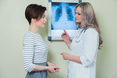 Doctor explaining diagnosis to her female patient analysing x-ray photography Royalty Free Stock Photos