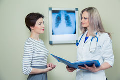 Doctor explaining diagnosis to her female patient analysing x-ray photography Royalty Free Stock Photography