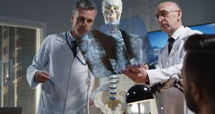 Doctor explaining diagnosis to his colleagues. Medium shot of a male doctor explaining diagnosis to his colleagues with a cervical spine x-ray and a skeleton royalty free stock image