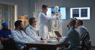 Doctor explaining diagnosis to his colleagues. Medium shot of a male doctor explaining diagnosis to his colleagues with a cervical spine x-ray and a skeleton stock photo