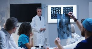Doctor explaining diagnosis to his colleagues. Medium shot of a doctor explaining diagnosis to his colleagues while writing symptoms on a whiteboard stock images