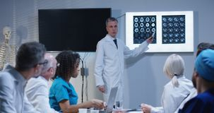Doctor explaining diagnosis to his colleagues. Medium shot of a doctor explaining diagnosis to his colleagues while writing symptoms on a whiteboard royalty free stock photo