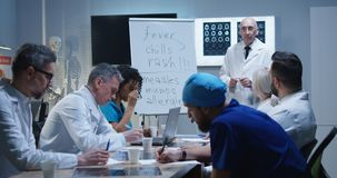 Doctor explaining diagnosis to his colleagues. Medium shot of a doctor explaining diagnosis to his colleagues while writing symptoms on a whiteboard stock photos