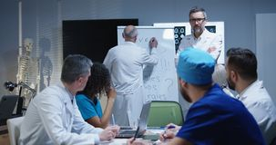 Doctor explaining diagnosis to his colleagues. Medium shot of a doctor explaining diagnosis to his colleagues while writing symptoms on a whiteboard royalty free stock photography