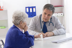 Doctor explaining diagnosis to his patient. Stock Image