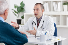 Doctor explaining diagnosis to his patient. Young doctor explaining diagnosis to his male senior patient Stock Image