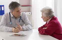 Doctor explaining diagnosis to his senior female patient Stock Images