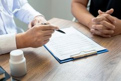 Doctor explaining and giving a consultation to a patient medical informations and diagnosis about the treatment for condition in royalty free stock photography